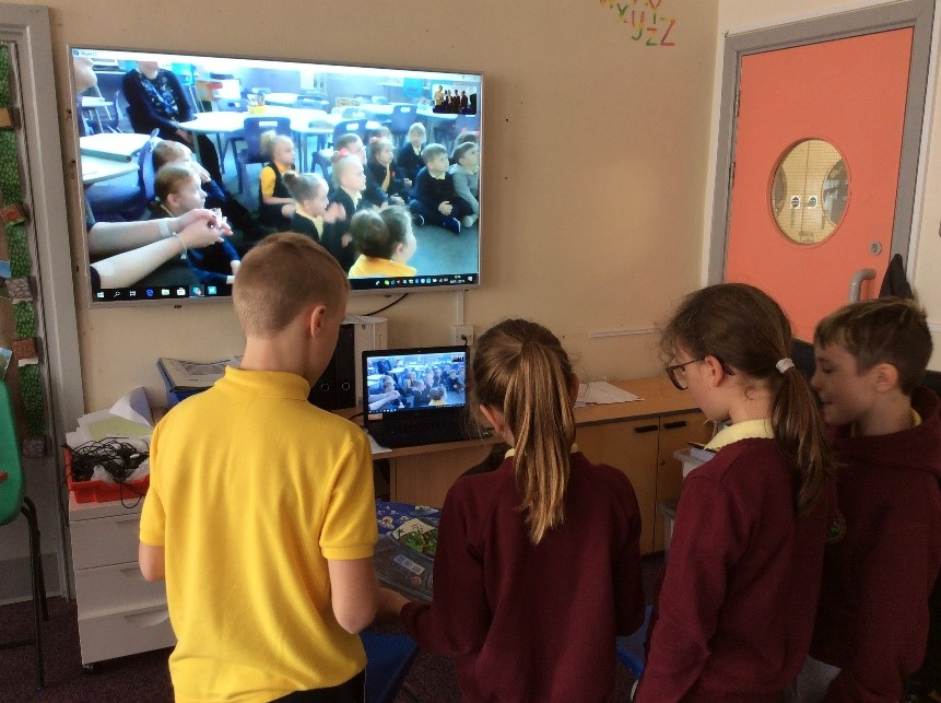 Darran Park Primary School students talk to other classes from around the world on Skype. A TV screen shows the students, while two girls and a boy face a laptop.