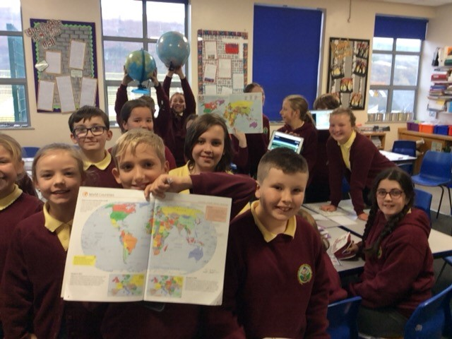 Darran Park Primary School students holding up globes and maps of the worlds
