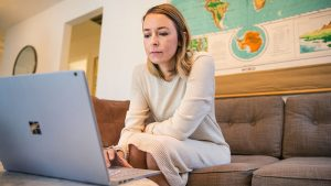 Women using Surface Book while sitting on couch.