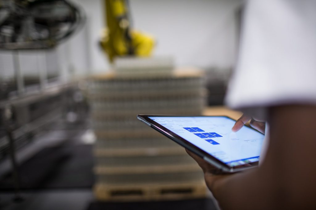 Photograph of a man using a tablet in the foreground in what looks like a factory or warehouse