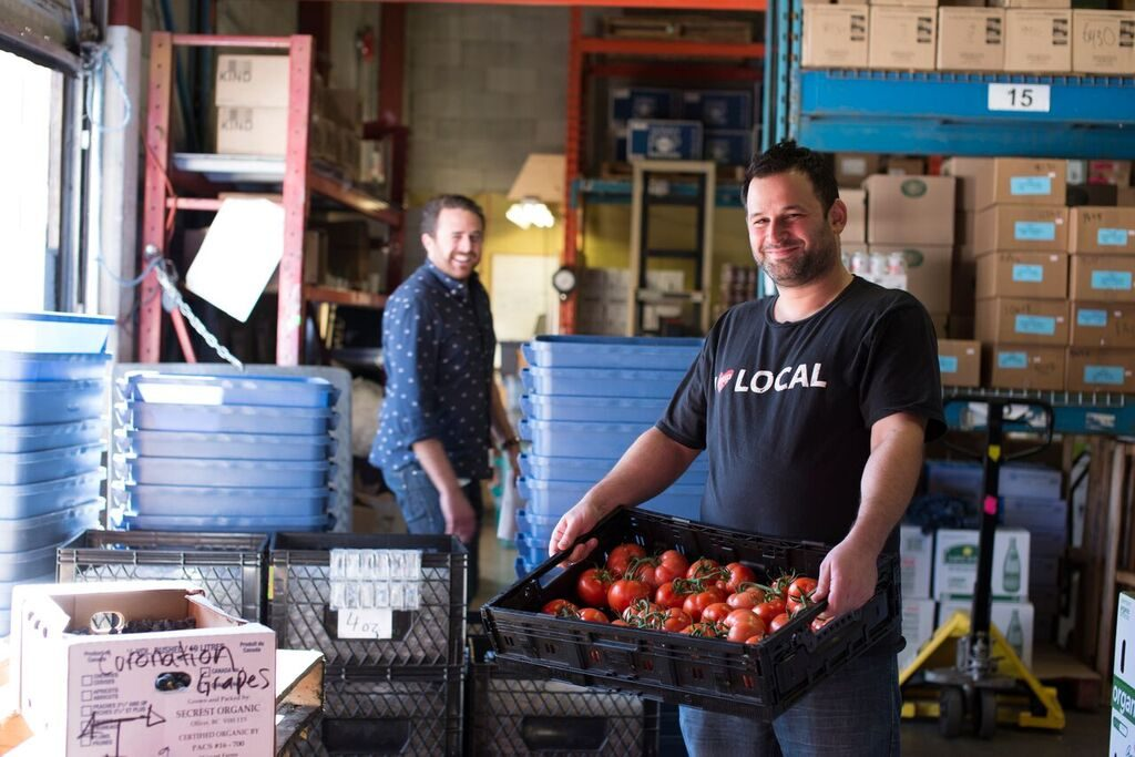 A photograph of two SPUD employees at work with one holding fresh tomatoes