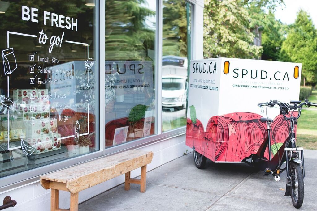 Photograph of a SPUD delivery ebike parked next to a Be Fresh retail store