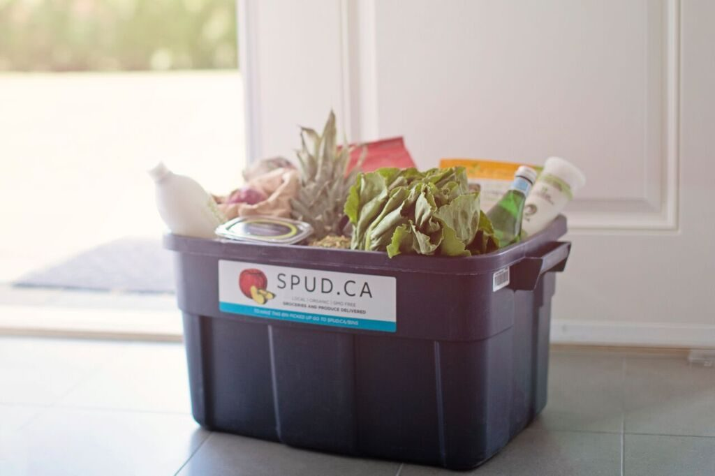 A plastic tote basket labelled as Spud.ca with fresh vegetables