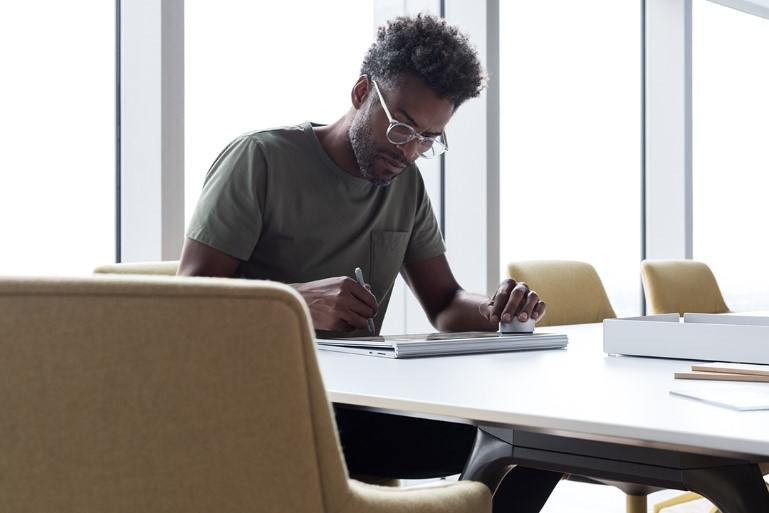 Photograph of a sitting man using a Surface Book