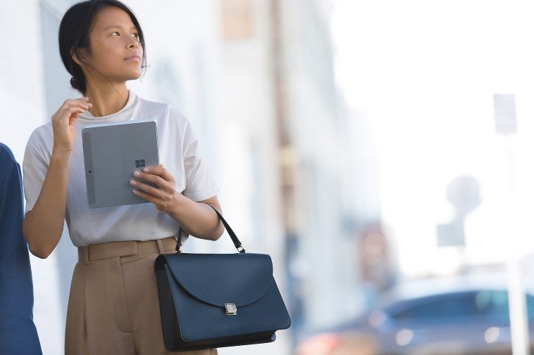 Photograph of a woman holding a Surface Go and a purse