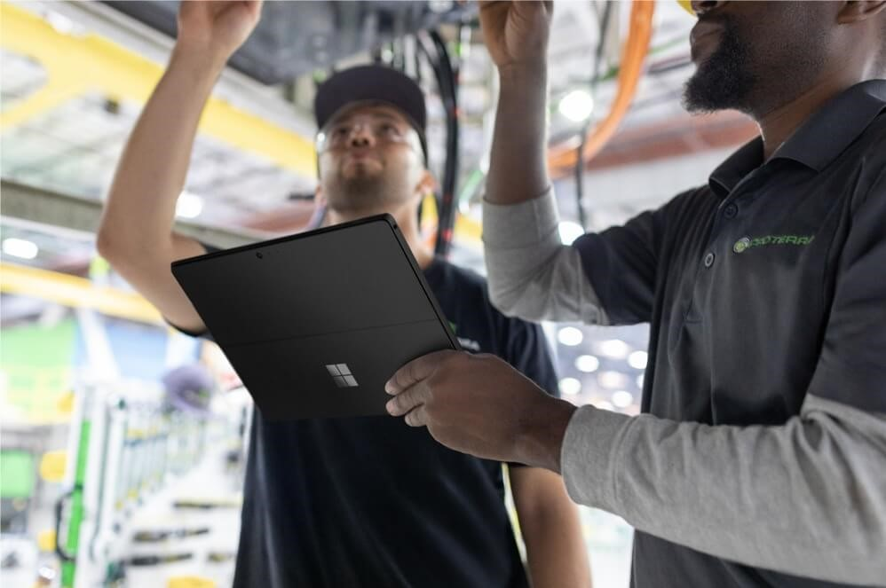 Photograph of two guys working in an industrial setting with one of them holding a Surface Pro