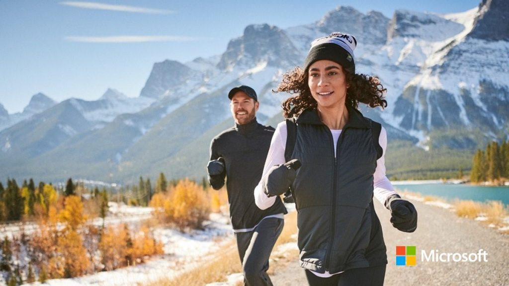 Photograph of a woman and a man running along a path with a snow-capped mountain range in the background.