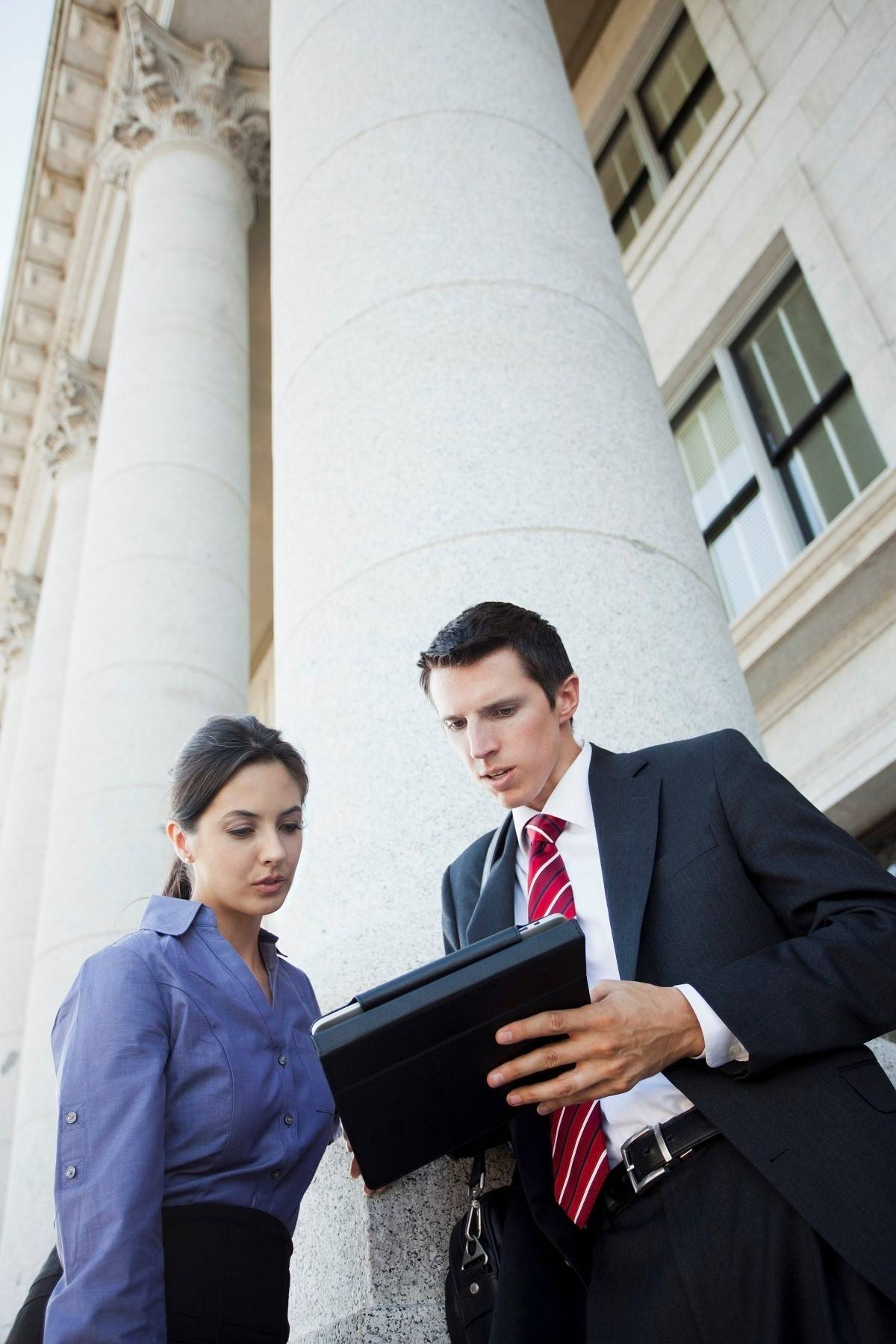 Two business people looking at a tablet on the steps of a building