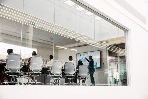 Employees sitting at table in meeting room with glass walls