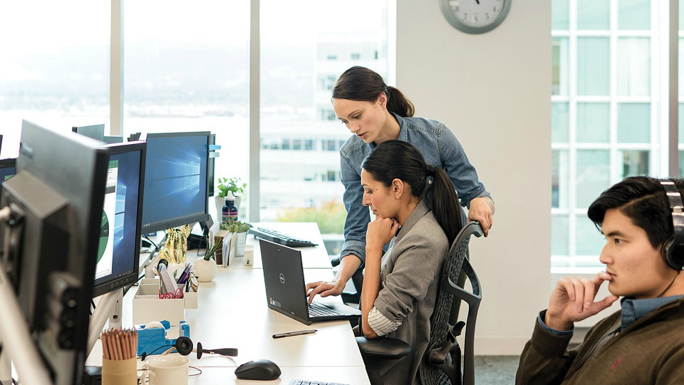 Two female employees on Windows machines in office