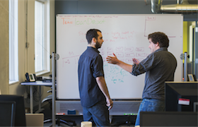Two men using a white board to sketch out product development updates.