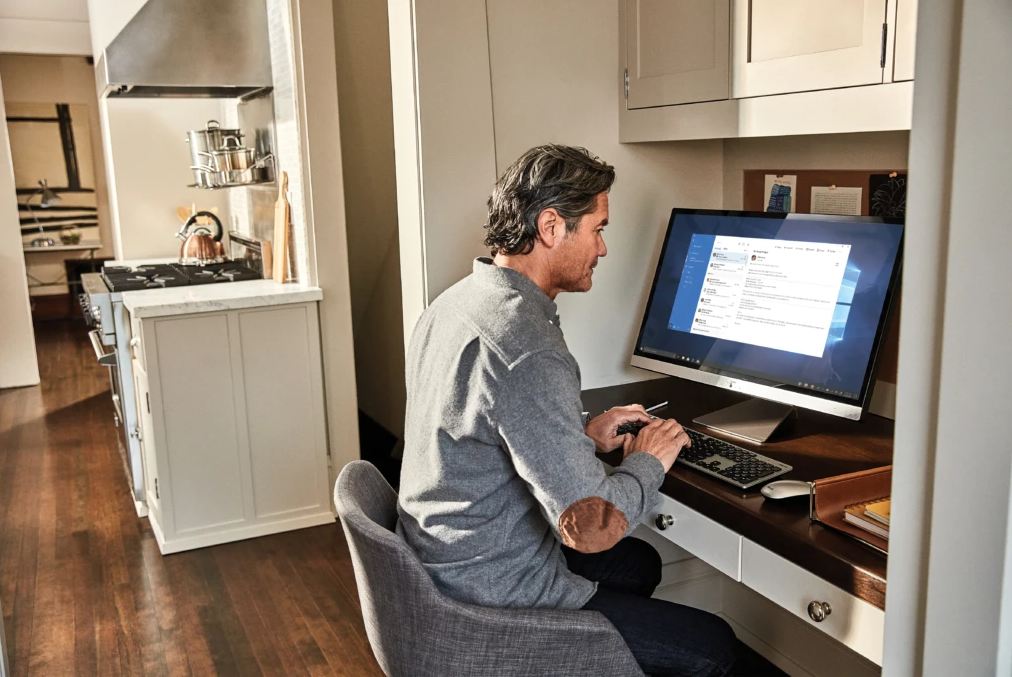 Man sitting at computer near kitchen.