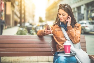 Image of a smiling woman sitting on a bench with headphones looking at a phone.