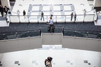 Image of two men walking and talking with each other in a corporate building.