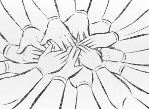 Hands stacked on top of each other in a huddle.
