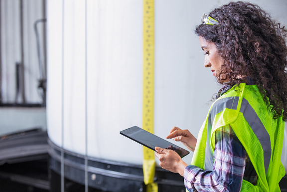 A field service worker in a yellow reflective vest working on a Microsoft tablet.