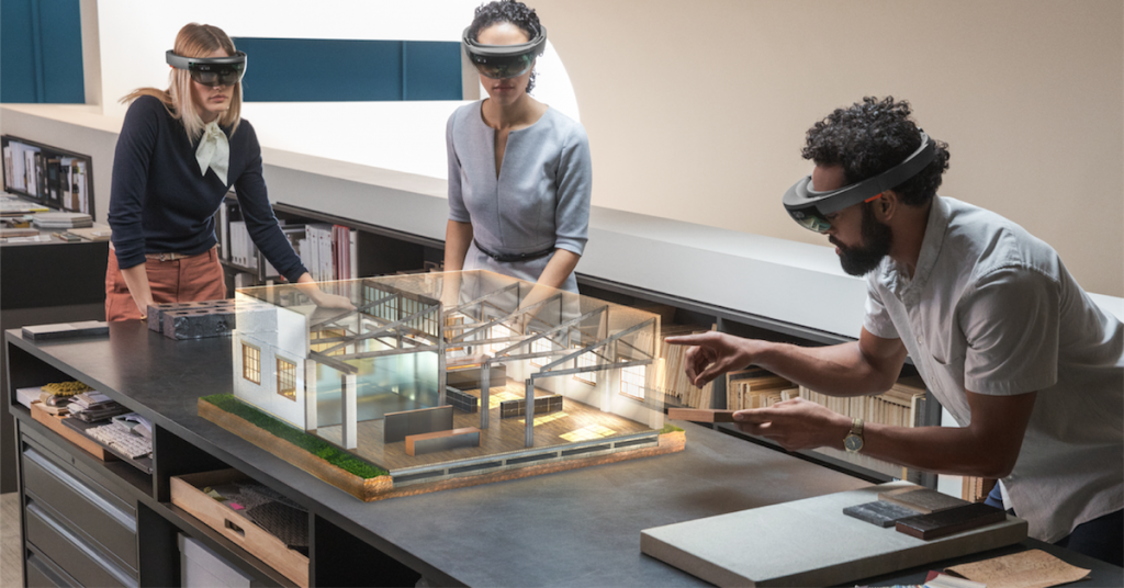 Three business people with mixed reality headsets on working on a virtual office building display.