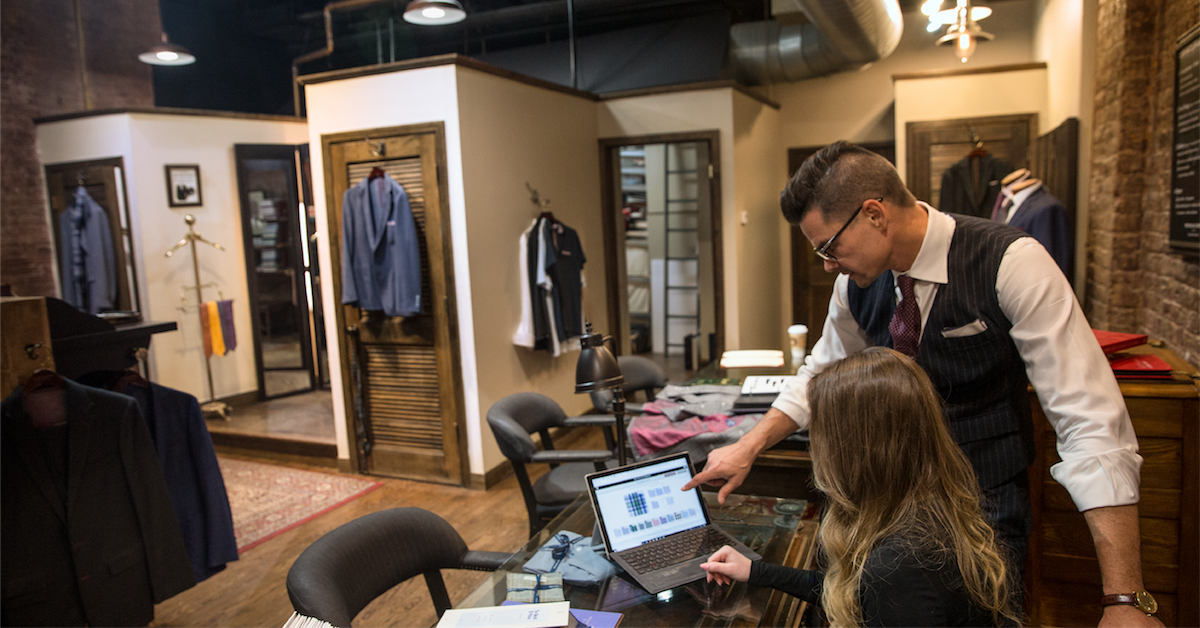 Two retail employees working from a Microsoft laptop in a high-end clothing store.