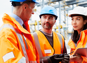 Three people in hard hats talking at a manufacturing plant.