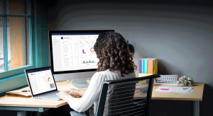 Woman sitting at desktop looking at Dynamics 365 Customer Service Insights