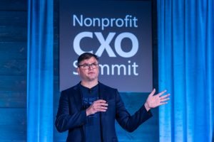 Photo of Erik Arnold on stage speaking at Nonprofit CXO summit
