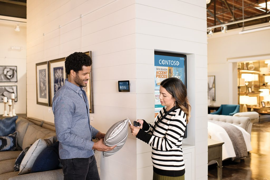 Two retail store employees scanning linen and pillows.