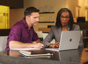Two people looking at a Microsoft laptop.