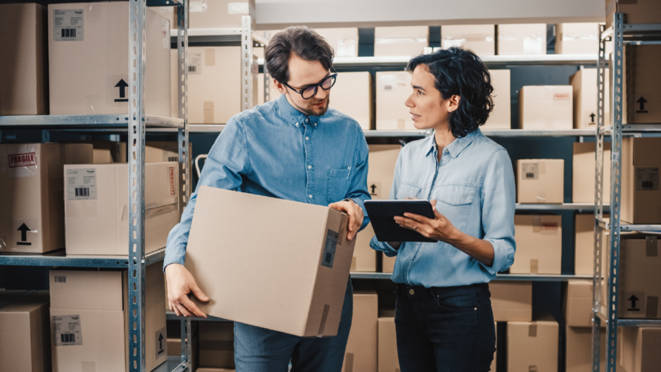 A man and woman in a warehouse reviewing shipment orders using Microsoft Dynamics 365 for Field Service.