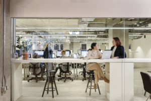 Two women sitting at a laptop in an open office space.