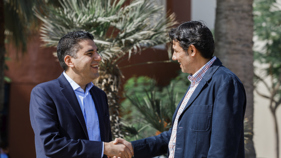 Two men in suits standing outside shaking hands.
