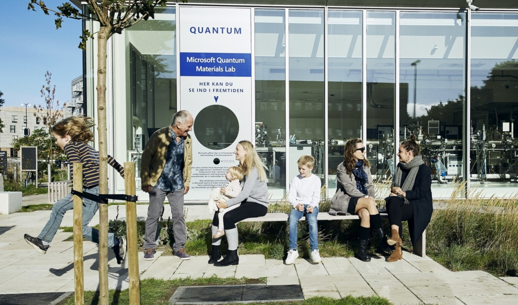 Adults and children congregating outside the the glass walls of the Quantum Materials Lab